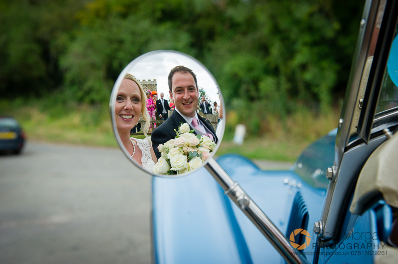 Bride and Groom in wing mirror of wedding car